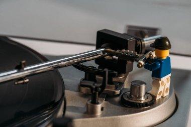 KYIV, UKRAINE - MARCH 15, 2019: close up view of plastic lego figurine fixing vinyl record player