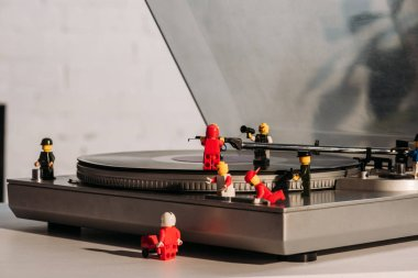 KYIV, UKRAINE - MARCH 15, 2019: colorful plastic lego figurines fixing vinyl record player