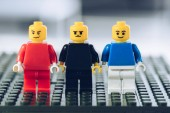 red, blue and black lego minifigures with various face expressions on lego blocks