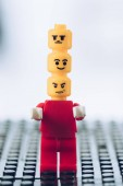 red lego figurine with indifferent, smiley and angry faces on heads