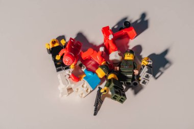 top view of scattered plastic lego figurines on white