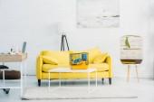 tágas, világos nappali sárga kanapéval, közel a fehér téglafal
