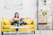 atraktivní žena s rozkošným synem na žluté pohovce v prostorných obývacím pokoji