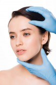 cropped view of plastic surgeon in blue latex gloves touching face of pretty woman isolated on white
