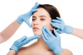 cropped view of plastic surgeons in blue latex gloves touching face of naked woman isolated on white