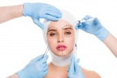 cropped view of plastic surgeons in blue latex gloves with medical equipment near face of woman with marks isolated on white