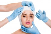 cropped view of plastic surgeons in blue latex gloves with syringe near face of woman with marks isolated on white