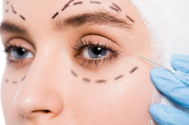 cropped view of plastic surgeon in latex glove holding syringe near face of woman with marks isolated on white