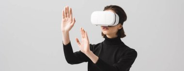 Panoramic shot of brunette young woman wearing virtual reality headset while gesturing isolated on grey stock vector