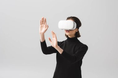 Brunette young woman wearing virtual reality headset while gesturing isolated on grey stock vector