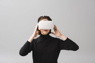 Young woman touching virtual reality headset isolated on grey stock vector