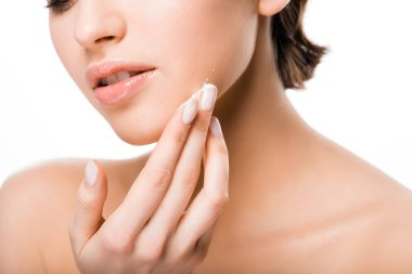 cropped view of woman applying face cream isolated on white
