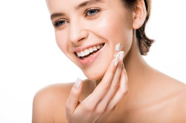 cheerful young brunette woman applying face cream isolated on white