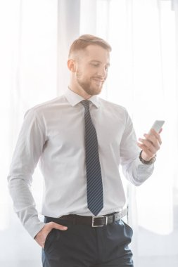 Cheerful bearded man in suit using smartphone while standing with hand in pocket stock vector