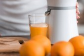 cropped view of woman near juicer and glass of orange juice