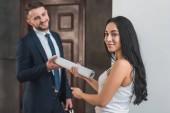 Selektiver Fokus attraktiver Brünetten, die dem Mann im Anzug Papierrollen geben