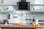 modern kitchen with juicer, glass and tasty organic oranges on wooden table