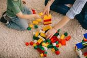 Vista ritagliata di mamma e figlio che giocano con i blocchi giocattolo sul tappeto