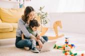 Mamma e figlio seduti sul tappeto e utilizzando laptop