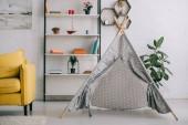 Fotografie graue Perücke neben Regalen mit Büchern und gelbem Sofa