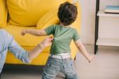 Oříznutý pohled na matku, jak si pohrává se synem v obývacím pokoji