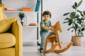 Cute child sitting on wooden rocking horse in living room