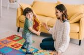 Sorridente madre e bambino giocare con lalfabeto tappeto puzzle
