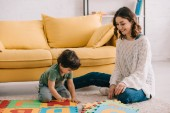 Usmívající se matka a dítě si hrají s abecedou puzzle