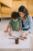 Mother and son drawing with color pencils in living room
