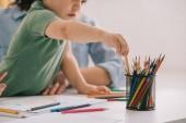 Fényképek vágott tekintettel az anya és fia rajz színes ceruzák a nappaliban