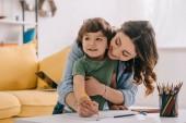 Madre e figlio disegno con matite colorate in soggiorno