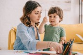 Fotografie amazed kid holding color pencil while drawing with mom