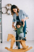 Kid on rocking horse holding hands with mom in living room