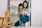 Mother and child reading book in living room