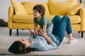 Felice madre e figlio giocare sul tappeto in soggiorno