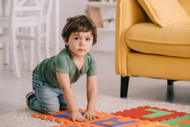cute kid in green t-shirt playing with puzzle mat
