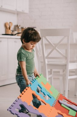 Cute child in green t-shirt playing with puzzle mat