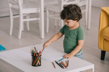 kid in green t-shirt with color pencils and papers in living room