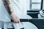 Fotografie cropped view of overweight tattooed man running on treadmill at sports center