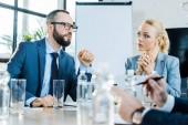 selektivní zaměření vousatého podnikatele hovoření poblíž spolupracovníků v konferenční místnosti