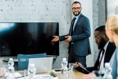 cheerful  business coach in eye glasses gesturing near tv with blank screen and multicultural coworkers