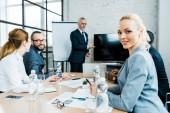 selektivní zaměření veselé obchodní ženy v blízkosti kolegů a obchodního trenéra v konferenční místnosti