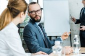 Photo selective focus of bearded man talking with woman near business coach in conference room