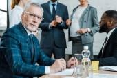 szelektív összpontosít szakállas üzletember a szem szemüveg nézett kamera közelében multikulturális munkatársak