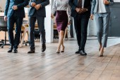 cropped view of multicultural businessmen and businesswomen walking in office