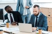 Ausgeschnittener Blick auf Businesscoach, der neben multikulturellen Mitarbeitern im Büro steht
