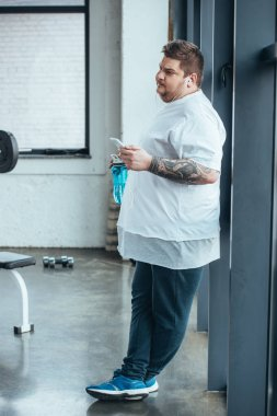 overweight tattooed man holding sport bottle and using smartphone at gym