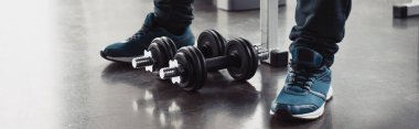 panoramic shot of man in trainers sitting with dumbbells at sports center