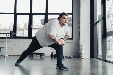 overweight tattooed man stretching legs at sports center