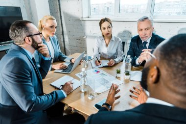 selective focus of businesswomen looking at african american coworker in conference room